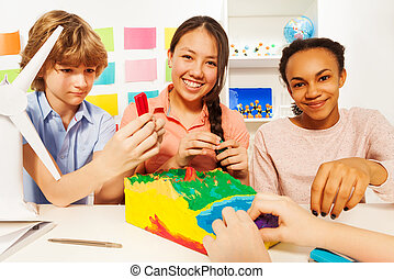 Three teenage kids modeling topographical relief - Three...