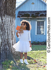 Kid toddler girl with autumn leaf playing outdoor park latin...