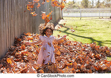 Toddler kid girl playing with autumn leaves latin ethnicity