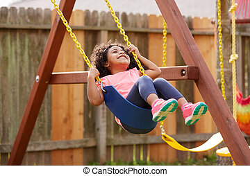 Kid toddler girl swinging on a playground swing in the...