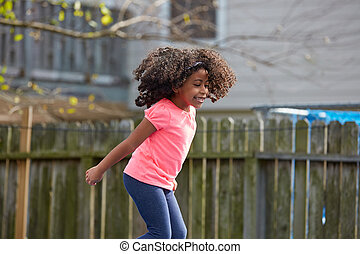 Kid toddler girl jumping on a playground