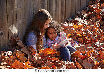 Kid girl friends playing tablet pc in autumn leaves - Kid...