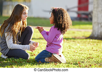 Kid girls playing in park grass mixed ethnicity