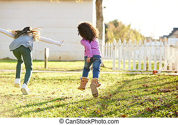 Multi ethnic kid girls playing running in park outdoor