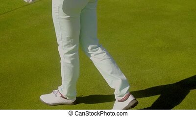 Close up on walking woman at golf course - Close up on shoes...