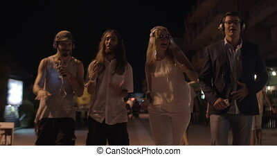 Young people dancing with music in night city - Steadicam...