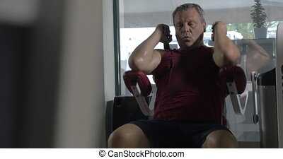Tired senior man training on exercise machine