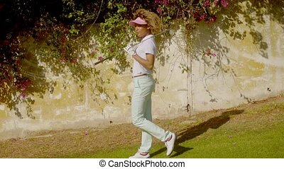 Woman golfer posing in front of bougainvillea - Young woman...