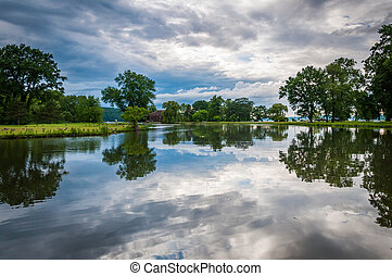 Storm clouds reflecting in a pond at Stewart Park in Ithaca,...