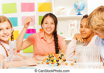 Asian teenage student in science class with flask