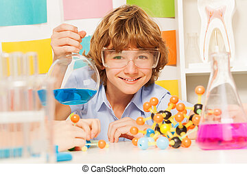 Boy in safety goggles holding flask at the lab - Young boy...