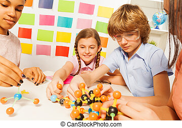 Young boy and girls assembling molecule model - Young...