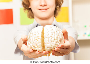 Smiling boy holding cerebrum model at his hands - Smiling 13...