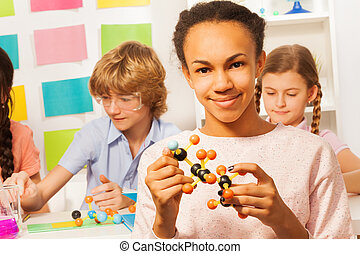 African student in a lab analyzing molecular model - African...