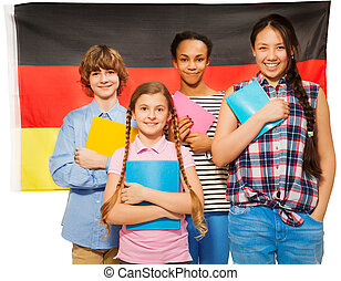 Four happy students standing against German flag - Four...