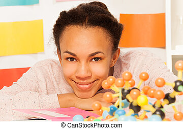 Schoolgirl with molecular structure at desk - Portrait of...