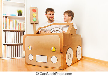 Father and his son driving handmade cardboard car at the...