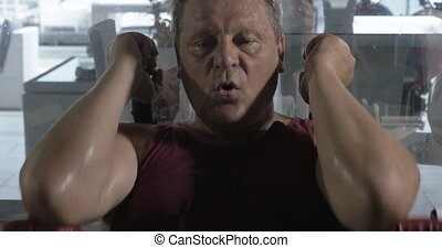 Man getting tired and sweaty training on fitness machine -...