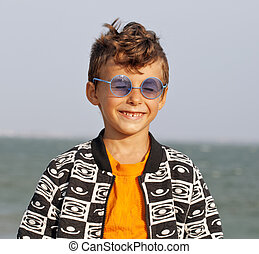 cute little boy at seacoast in fashion clothers and blue...
