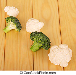 Fresh broccoli and cauliflower on background of light wood....