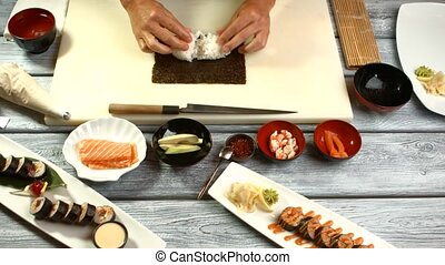 Man's hands cooking sushi.