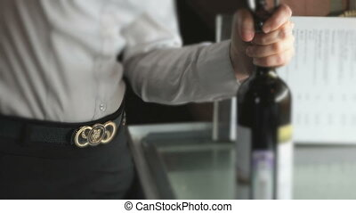 Hand opening the wine bottle using the corkscrew