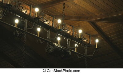 Wooden ceiling with lamps in the form of candles at a fancy...