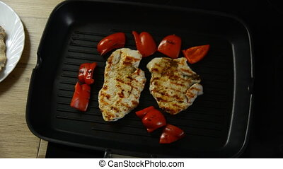 Turkey fillet cooking on grill. slices of pepper on the...