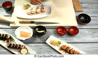 Hand puts caviar onto sushi. Plate with small sushi rolls....