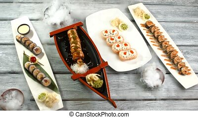 Plates with sushi rolls. Japanese food on wooden background....