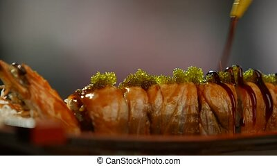 Tool pouring sauce on sushi. Sushi rolls with shrimp. Green...