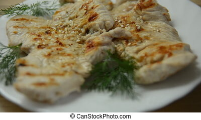 Roasted chicken meat on a plate dressed with sesame seeds...