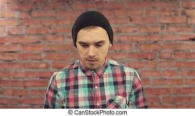 Young blogger in black hat, plaid shirt come closer to...