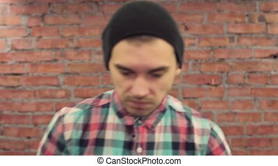 Blogger in black hat, plaid shirt stand in front camera,...