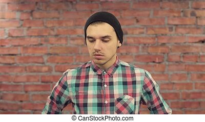 Young blogger in black hat, plaid shirt stay in front of...