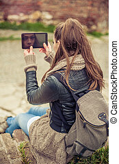 Woman is reflected on the screen of her mobile phone -...