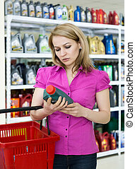 blonde girl chooses motor oil in auto parts store
