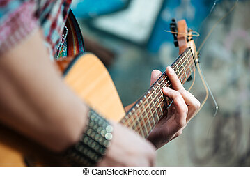 Male hands playing on guitar outdoors - Closeup portrait of...