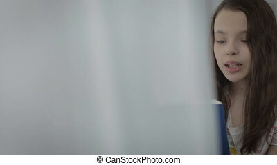 Beautiful little girl reading an interesting book by window...