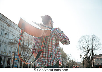 Man walking with guitar outdoors - Rear view portrait of a...