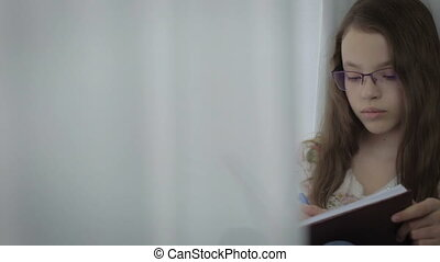 Serious little girl in glasses diligently does her homework at window.