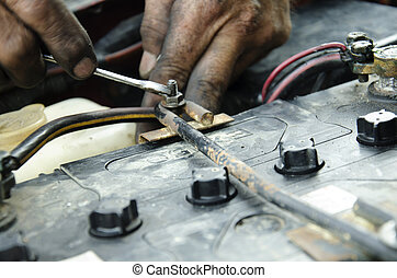 professional automotive motor mechanic repair and inspecting the car battery