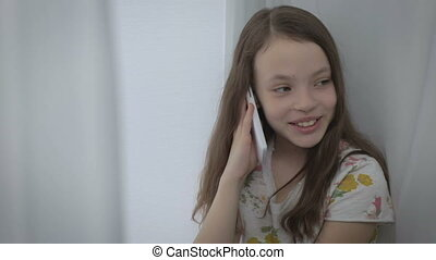Beautiful little girl emotional talking on smartphone and...