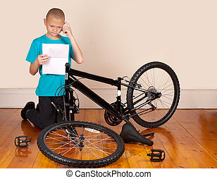 Boy assembles new bicycle - A young boy is frustrated by the...