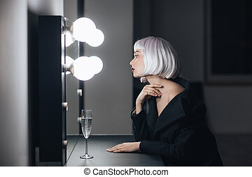 Blonde woman sitting and looking at mirror in dressing room...