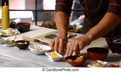 Male hands making sushi rolls Man cooking japanese food Best...