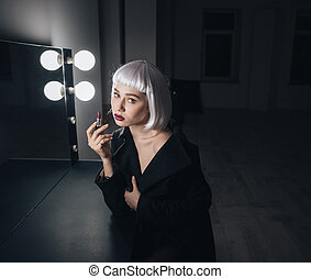 Tender woman in blonde wig applying lipstick near the mirror...