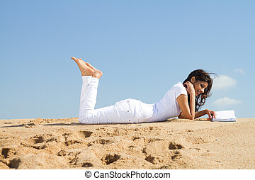 woman relaxing on beach with book and lying down