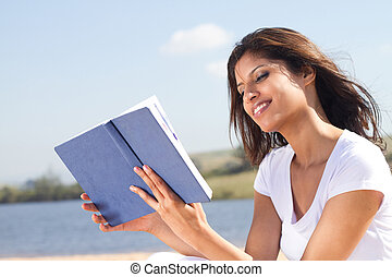 beautiful arabic woman reading book on the beach