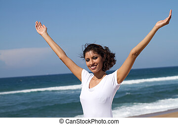 indian woman with arms outstretched on the beach
